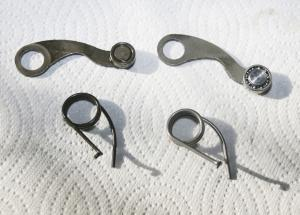 The Factory Pro Shift Kit (right) with its roller-bearing shift arm and stronger spring, compared to the OEM parts (left).