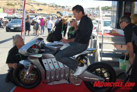 Michael Czysz takes notes while sitting aboard his remarkably attractive E1pc electric-powered motorcycle. Czysz would take the win in the FIM e-Power electric motorcycle race with a last-seconds pass on Michael Barnes whose bike simply ran out of power yards from the finish.