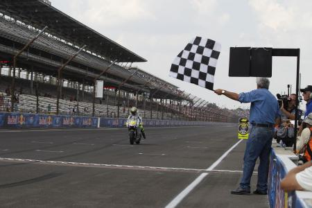 Grand Marshal Jay Leno waves the checkered flag as Valentino Rossi crosses the finish line.