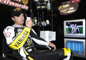 Colin Edwards does his best Bruce Allen impersonation, lounging comfortably with a beverage watching the coverage on the monitor.
