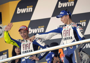 "Valentino Rossi waves to the crowd from last year's Jerez podium. Jorge Lorenzo prefers the old ""point at random people in the audience"" move."