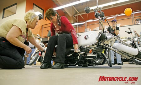 An employee at St. Augustine Harley-Davidson teaches a female rider how to pick up a downed motorcycle. The company is focusing on encouraging women to ride and teaching them the necessary skills in a friendly environment.