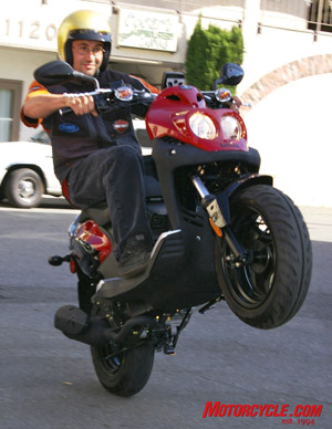 "This proves that, yes, wheelies are possible with scooters, this time aboard a 110cc two-stroke ""Rattler"" that features a remote-reservoir adjustable shock, digital instruments, front disc brake and nimble handling. Price tag is about $2600."