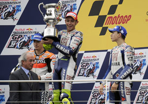 Valentino Rossi (with trophy) celebrates his win on the podium with teammate Jorge Lorenzo (right) and the Ducati-bound Nicky Hayden.