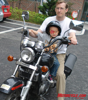 The author and his daughter aboard the Kimchi Piglet, a 125cc Hyosung.