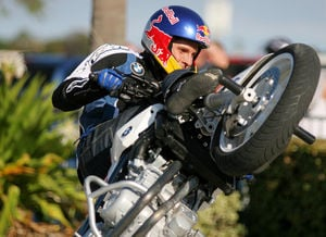 Christian Pfeiffer executes a circle wheelie while sitting on the tank of his BMW F800S.