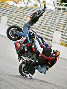 "Josh ""Crazy"" Conway of the Orlando-based Warped Toys stunt team performs a wheelie with two passengers at Stunt Fury 2007, held during Daytona Bike Week."