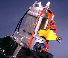 The curved yellow valve rotates on a pivot to open and close the exhaust port; it is shown in the closed position.