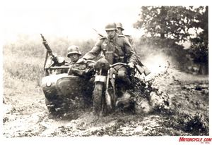 Trained to meet all challenges, the sidecar teams sloshes through muddy bog in what is most likely a scene from pre-war training as the soldiers are wearing early style WW1 helmets.
