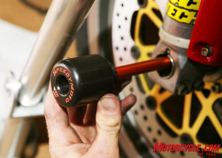 These front axle sliders by Speedy Moto keep critical front end parts, like rims, forks and braking components, from contacting the pavement in the event of a crash. (Photo by Holly Marcus)