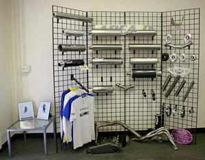 A display rack in the waiting room shows off some of Area P�s products - a few complete mufflers, as well as some of the components used to build them (perforated cores, billet end caps, exhaust hanger brackets) and offers a small selection of Area P apparel. The headers lying on the floor are prototypes Area P built while working towards a final design for a customer.