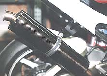 The unit in this photo, also offered with a carbon canister, is bolted onto a Graves Yamaha R1 race bike, but the R6 canister will be the similar. Notice the slotted clamp holding the canister on the exhaust bracket. A rubber grommet beneath the clamp protects the canister from scratching and dampens some vibration.