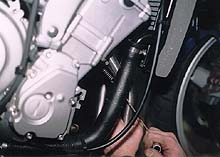 Here, a spring puller is being employed to connect the outside spring to the head pipes. This system of installation can be much easier to deal with than head pipes that bolt directly to the manifold.