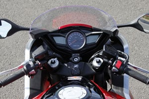 Dual LCD info screens flank the central analog tachometer.