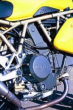 Notice the forward pivoting rear brake lever, forward canted engine and trellis frame.