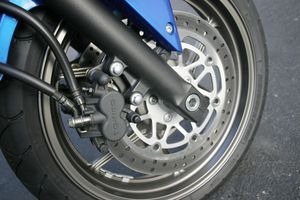 Rubber brake lines and sliding-pin, two-piston calipers function but lack feel and require a nice, strong pull on the lever.