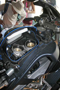 You're looking at a cutaway that shows the gaping 61mm throttle bodies positioned where you'd normally find a fuel tank. The lower end of the picture shows a cutaway of the frame that serves as the actual fuel tank.