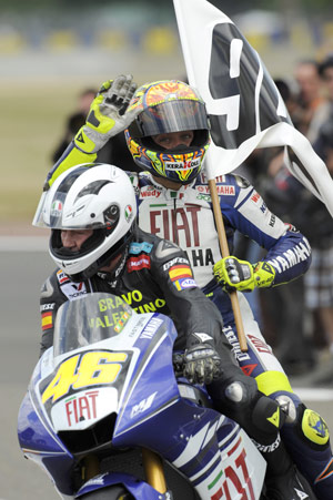 Valentino Rossi lets Ángel Nieto take the controls in a victory lap celebrating his 90th career victory.