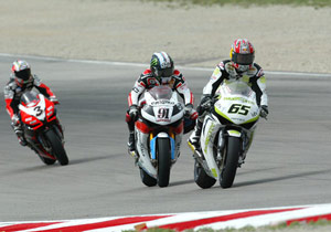 Honda riders Leon Haslam (91) and Jonathan Rea (65) battle while Aprilia's Max Biaggi (3) closes in.