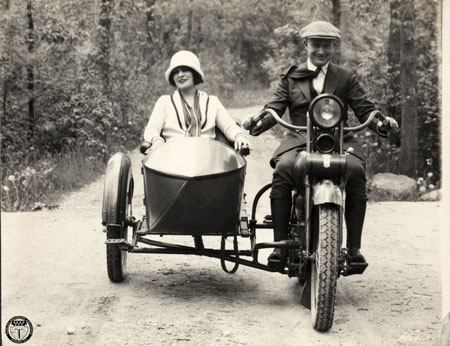 Hap Jameson, editor of the Harley-Davidson Enthusiast, rides a motorcycle with Harley-Davidson motorcycle with sidecar in 1925. Copyright Harley-Davidson.