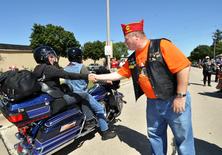 American Legion National Commander Clarence Hill greets one of the participants of the charity ride.