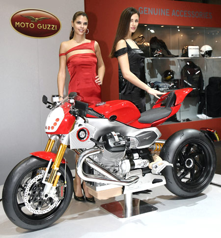 "Take your eyes off the two models and you'll notice the Moto Guzzi V12 LM's LED headlights and LCD ""mirrors""."