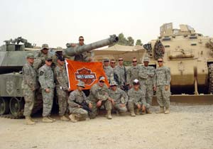 A military unit displays the flag they received from Harley-Davidson.