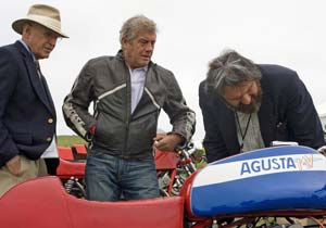 Lifetime Achievement Award recipient Giacomo Agostini (center) inspects a bike with two judges.